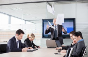 Mad CEO throwing documents at a meeting. Subordinates looking do